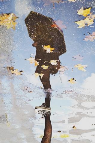 Foto e poster di una ragazza con l'ombrello riflessa in una pozzanghera