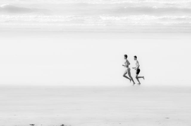 Foto e poster in bianco e nero di due ragazzi che corrono sulla spiaggia