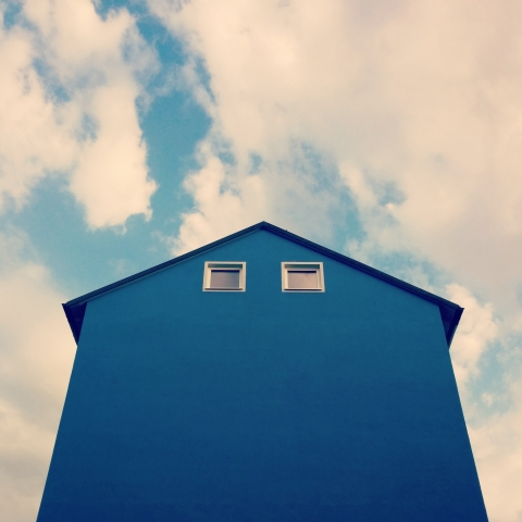 Foto e poster di una casa blu su cielo blu