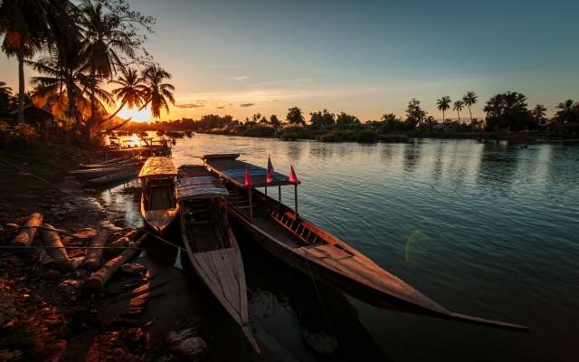 Long Boats at sunset over Mekong River